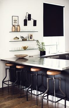 Open plan kitchen in a Manhattan loft apartment (designed by Nate Berkus & Jeremiah Brent). Industrial bar stools with neutral tones and clean lines