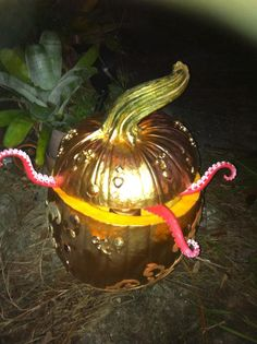 I found a pumpkin at Whole Foods with a crazy stem, glued rhine stones, etc on, spray painted the whole thing gold, found the Squid fingers at Sam Flax, and on Halloween night I found a box of glow bracelets at Michael's in the dollar section and threw them inside for an eerie glow.