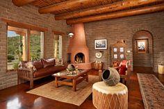 cheminée d'adobe couleur terre cuite dans le salon aménagé avec un canapé en…