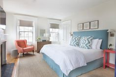 Three sea fan art pieces hang above a blue headboard accenting a bed dressed in a blue bedskirt and white hotel bedding complemented with blue ikat pillows.