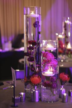 Other tables will have a trio of cylinder vases with submerged purple orchids and topped with floating candles. Surrounded by skinny cylinders with submerged orange pincushions topped with floating candles and silver mercury glass votives