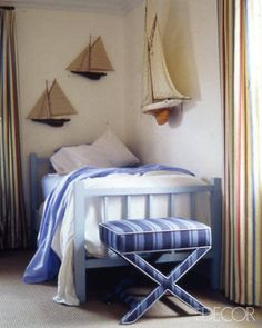 Steven Gambrel designed a Hamptons cottage infused with a maritime motif. In a guest room, model boats are displayed on the walls.