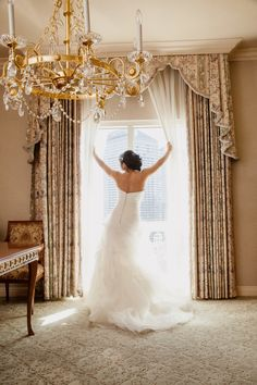 Always a classic image of the bride pulling back the drapes of a window. Las Vegas Wedding Planning by Andrea Eppolito Photo by Adam Frazier Photo