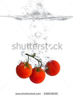 red cherry tomatoes splashing water - stock photo