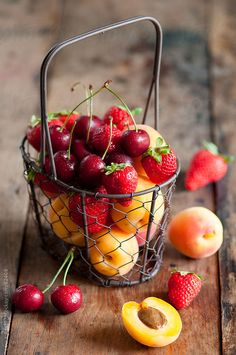 a metal basket full of summer fruit by Laura Adani photography - www.lauraadani.com