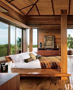 Dark-stained cedar walls and a rattan ceiling wrap the master bedroom of the spa villa in warm tones and textures | archdigest.com