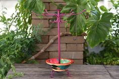 A large jewelry stand with metal hooks to hang necklaces from and a bowl at the bottom to hold smaller jewelry pieces.