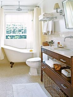 An antique English buffet table was transformed into a contemporary sink console, giving this bathroom a distinctly modern feel. A ceiling-mount shower fixture and a track curtain turned a simple white slipper tub into a stand-up shower. Used as a guest bathroom, the wall sconces, waffle towels, and silver accents make this room seem like a luxury hotel bathroom.