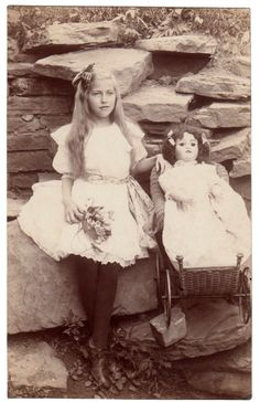 Girl with her doll and her pram. 1910. Posed picture with rock under stroller's wheel.