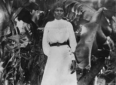 A South Sea Islander woman standing among banana trees at Farnborough, Queensland, around The woman is dressed in western fashion - a dress with a la. Glasshouse Mountains, Forced Labor, Woman Standing, South Seas, First Nations, Western Wear, Vintage Photos, Style Icons, The Past