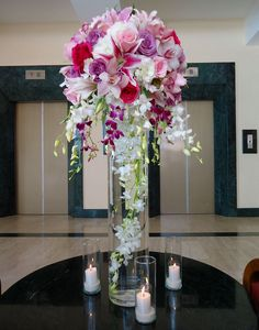 "Tall Centerpiece, 31"" height vase with a white Dendrobium large strand submerged Lilac, pink & fuchsia Roses, Stargazer Lily, and fuchsia & white hanging Dendrobium."