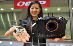 Wearables, drones, talking robots take center stage at International Tokyo Toy Show | A CCP Co. employee shows off the Nano Falcon DigiCam, a remote-controlled copter that can shoot photos or videos from the air. The 20-gram drone can also be folded up and snapped into the open cavity in the control unit to form a hand-held digital camera.