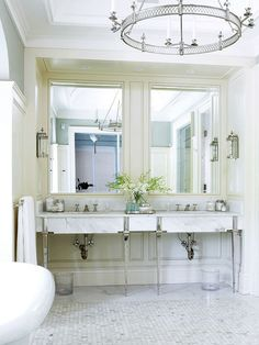 Elegant bathroom with Carrara Marble and polished nickel. The sconces give style while the overhead baby cans provide task lighting. The fabulous large polished nickel chandelier gives the finishing touch of luxury.