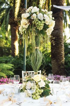 A tall centerpiece of roses and fresh green grapes is covered in grass.