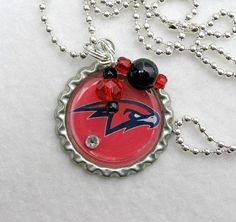 NBA Atlanta Hawks Basketball Necklace by Sports Jewelry Studio.  Go Hawks! Support your NBA Atlanta Hawks with this cute Hawks basketball 1-inch bottle cap necklace with glistening crystals and glass beads in the team colors. A sparkling rhinestone is added on top for extra Bling! 24-inch silver plate ball chain, which can be easily shortened with scissors if you like.  Free Gift Wrap! Quick Shipping!  Water resistant but not waterproof.  Not affiliated with, nor licensed by, NBA or the…
