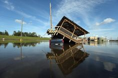 A partially submerged truck and gazebo are seen in Hurricane Isaac's flood waters with a flooded chemical plant in the background on September 1, 2012 in Braithwaite, Louisiana. Louisiana residents co