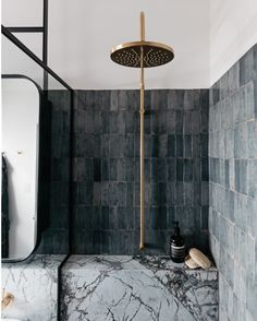 Charcoal walls and metallic shower fitting. For more, visit houseandleisure.co.za
