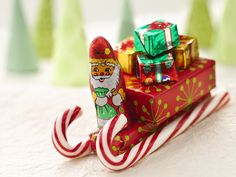 Santa's Candy Sleigh: Glue gun and glue sticks; 8 candy canes, 6 inches long; 4 bars (2.07 ounces each) chocolate-covered peanut, caramel and nougat candy; 4 packages (1½ ounces each) raisins; 4 foil-covered chocolate Christmas trees (1.3 ounces each) or 12 foil-covered chocolate gift packages; 4 foil-covered peanut butter or chocolate Santas (1 ounce each)