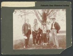 This is a group portrait of two Native Americans and two white men. Identified are Plenty Horse and his wife, Roan Horse. They are standing nearest to a tree and dressed in traditional clothing of the tribe. The two men on either side are wearing suits with hats. Plenty Horse was the man who killed Lieutenant Casey after the Wounded Knee massacre, his wife was wounded and crippled in that action. Date 	circa 1900: