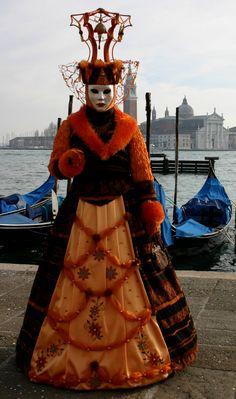 https://flic.kr/p/4v49LA   Lady in orange in front of a gondola (IMG_3929a)   Taken at the Carnivale in Venice, Italy in January 2008.