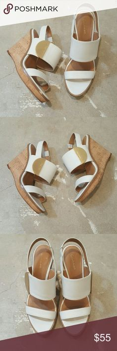White Calvin Klein Wedge Sandals I am selling a preppy and chic pair of Calvin Klein Wedge Sandals. This designer is known for clean lines and sexy silhouettes, this particular pair of shoes exemplify both beautifully.  Excellent condition worn once, minimal signs of wear on sole, only!!  Last photo shows a little adhesive seeped out where stretchy band meets leather, I bought this way and you can not tell at all when on.  Does not affect wear!!  I love the gold accents paired with the white…