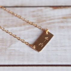 Arrow Stamped Mini Bar Necklace Personalized Gold-Filled Short Bar Necklace   This delicate everyday necklace is the perfect gift for those who want to always have a reminder of the most important dates close to their heart.   -Gold-Filled Rectangle 16x6mm (gold filled jewelry is tarnish resistant) -Can be hand stamped with up to 4 characters: letters, numbers, heart stamp, or one arrow stamp (as shown).  -Gold-filled 1.6mm flat cable chain. -Every necklace comes tucked inside a cotton…