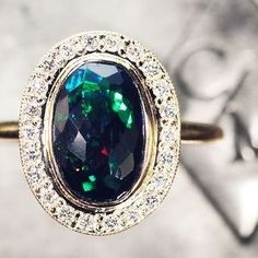 Our 1.37 carat black Opal ring with diamond halo.  chincharmaloney.com