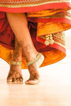 Beautiful shot of the mehendi on the feet with the gold payal. Love the position of the feel as well.