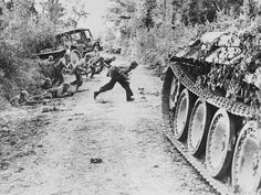 American soldiers race across a dirt road, which is under enemy fire, nearSaint-Lô, july 25, 1944. Other Yanks crouch in ditch before making the crossing, too. In the left background is an American truck which has been hit and partially burned.
