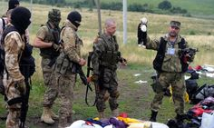A pro-Russia militant holds up a stuffed animal as others look on at the site of the crash of a Malaysian airliner carrying 298 people from Amsterdam to Kuala Lumpur in Grabove, in rebel-held east Ukraine. Cigarettes are a nice respectful touch...
