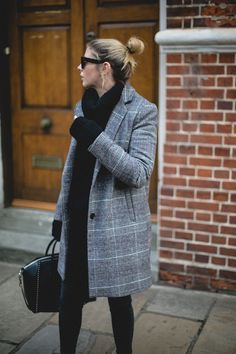 Emma Hill wears check coat, chunky black knit jumper, Celine sunglasses, black jeans, cosy winter outfit