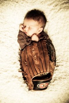 Baby snuggled in daddy's baseball glove or mommy's softball glove.