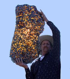 A man holds a 3-foot slab of the Fukang Pallasite. Pallasites are meteorites made up of large olivines in an iron-nickel matrix, and they're fairly rare. Only 61 have been found however, many of those have been large enough that thin sections are distributed in museums all over the world.