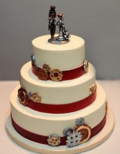 I really really like the simplicity of this cake.  Don't like the topper and color should be forest or emerald green, possibly black.  Gear use excellent. (Steampunk Wedding Cake - New Renaissance Cakes.)