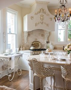 Whispers of Alabaster - Rustic yet refined, a marble-topped tea cart, a black chandelier dripping with crystals, and a pair of lattice-backed counter stools make a charming trio in classic wrought iron.