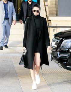Kendall Jenner wears a black mini dress, long coat, white Céline sneakers, and a Birkin bag