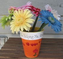 ink pen flower pot gift for a teacher.  Get fake flowers from Michael's.  Wrap the pen with green flower tape from the ink to the top to keep the flower on.  Buy polished rocks from Michaels to keep the pens upright.