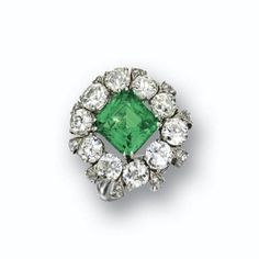 EMERALD AND DIAMOND RING, CIRCA 1935 Set in the center with a rectangular mixed-cut emerald weighing approximately 3.75 carat, framed by 10 old European-cut diamonds weighing approximately 4.20 carats, above an open gallery of petal motif set with single-cut diamonds weighing approximately .90 carat, mounted in platinum