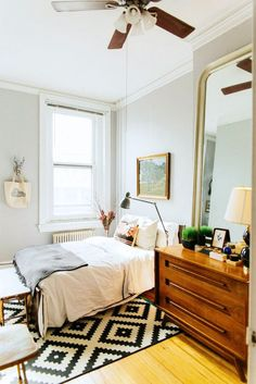 Homey bedroom with neutral bedding, framed art, and gold IKEA Songe mirror.