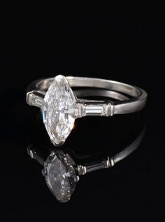 ART DECO PLATINUM MARQUISE DIAMOND RING: Platinum ring centers a solitaire marquise cut diamond of approx. .90 Ct., rated VS2 in clarity and H color. Flanked by 2 baguette diamonds. Weight 3.4 grams.