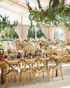A tent draped with natural-toned, gauzy fabric accommodated guests for the reception. Three oversized chandeliers were hung down and adorned with seasonal birch branches, moss, and smilax vine.