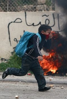 A Palestinian schoolboy runs past a burning tire during clashes between Israeli troops and Palestinian stone throwers in Hebron We were unable to find any information about the photographer. Does anyone know?