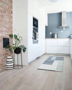 Rustic exposed brick wall goes very well here with Modern white kitchen. Love the grey painted backsplash.