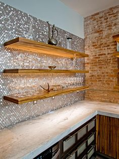 "Penny tiles add glamorous shimmer to a kitchen with a reclaimed-rustic vibe. ""The black limba floating shelves are fitted with recessed LED lighting that highlights the penny tiles and makes them shine,"" says Patrick Kennedy of Superior Woodcraft."