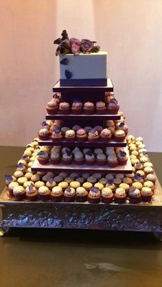 Purple and white wedding cake with a cupcake tower below - SFCS