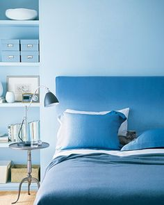 Using Ombre - The gentle progression of color in ombre suggests the transition from wakefulness to slumber, especially in soothing shades of blue. The headboard slipcover and matching pillowcases are shrouded in sky-blue linen that's dyed a deeper, sea-inspired tone, embodying the spare beauty of a monochromatic palette.