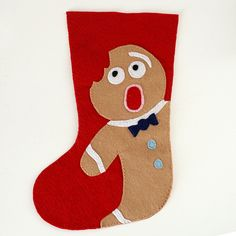 red felt stocking with distressed gingerbread man with a bite taken out of his head More