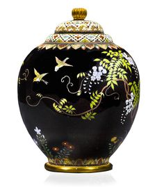 Vase and cover by Namikawa Yasuyuki The compressed ovoid vase with a tapered foot and worked in colored enamels and silver wire with a continuous design of sparrows in flight by a dense vine of flowering wisteria and stands of chrysanthemums, snap dragons and bell flowers, all against a midnight blue ground, the shoulder and foot decorated with stiff leaf bands and the rim and cover designed with floral lozenges, chrysanthemum finial