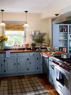 Cozy and Cheerful. A mix of old and new warms this Sag Harbor cottage's country kitchen, with mahogany countertops, stainless-steel appliances, and the dusty blue cabinets. Creamy beadboard walls and open shelves keep the room light. Blue Kitchen Cabinets, Kitchen Cabinet Colors, Kitchen Paint, New Kitchen, Kitchen Ideas, Dark Cabinets, Awesome Kitchen, Cheap Kitchen, Kitchen Rug