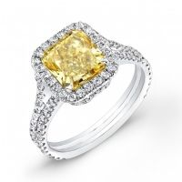 A combination of fire and beauty radiates from this lovely 1.82 Ct. diamond engagement ring. Its center gem is a stunning 1.02 Ct. Radiant cut canary diamond with VS1 clarity and natural Fancy Yellow color grade. Around the center gem is 0.80 Ct. Round cut diamonds which also line the split shank in U-setting. The side diamonds have F-G color grade and VVS2-VS1 clarity to complement the center stone. Available in 14K white or yellow gold or 18K white or yellow gold or platinum!